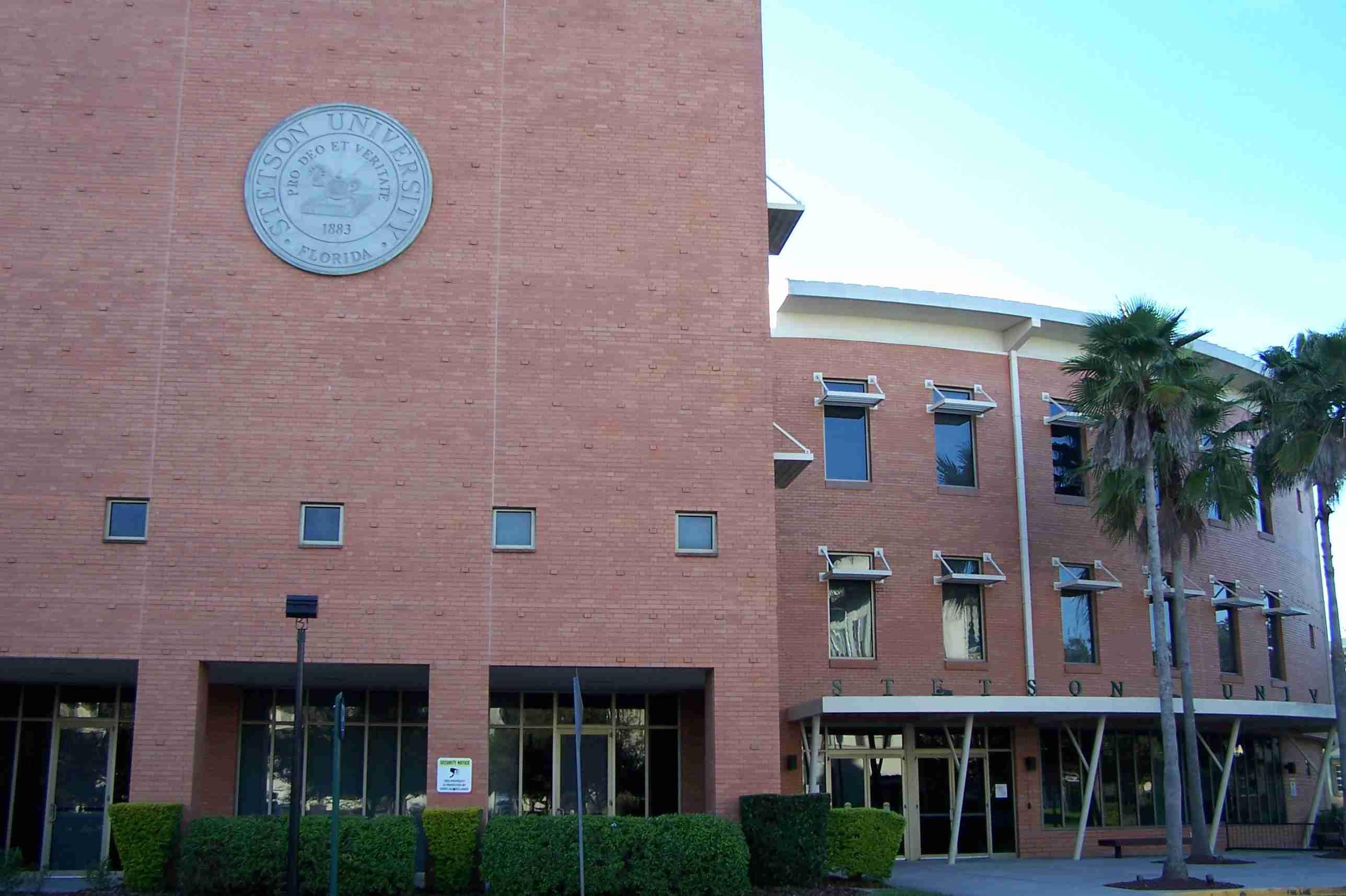 Fachada de ladrillo con emblema, edificio de ladrillo curvo adjunto