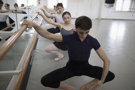 Ballet dancers practicing plie at barre in dance studio