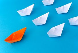 White origami boats follow an orange one over blue background