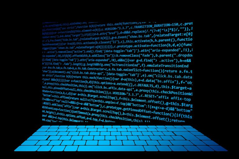 Programming laptop screen and lit keyboard on a black background.