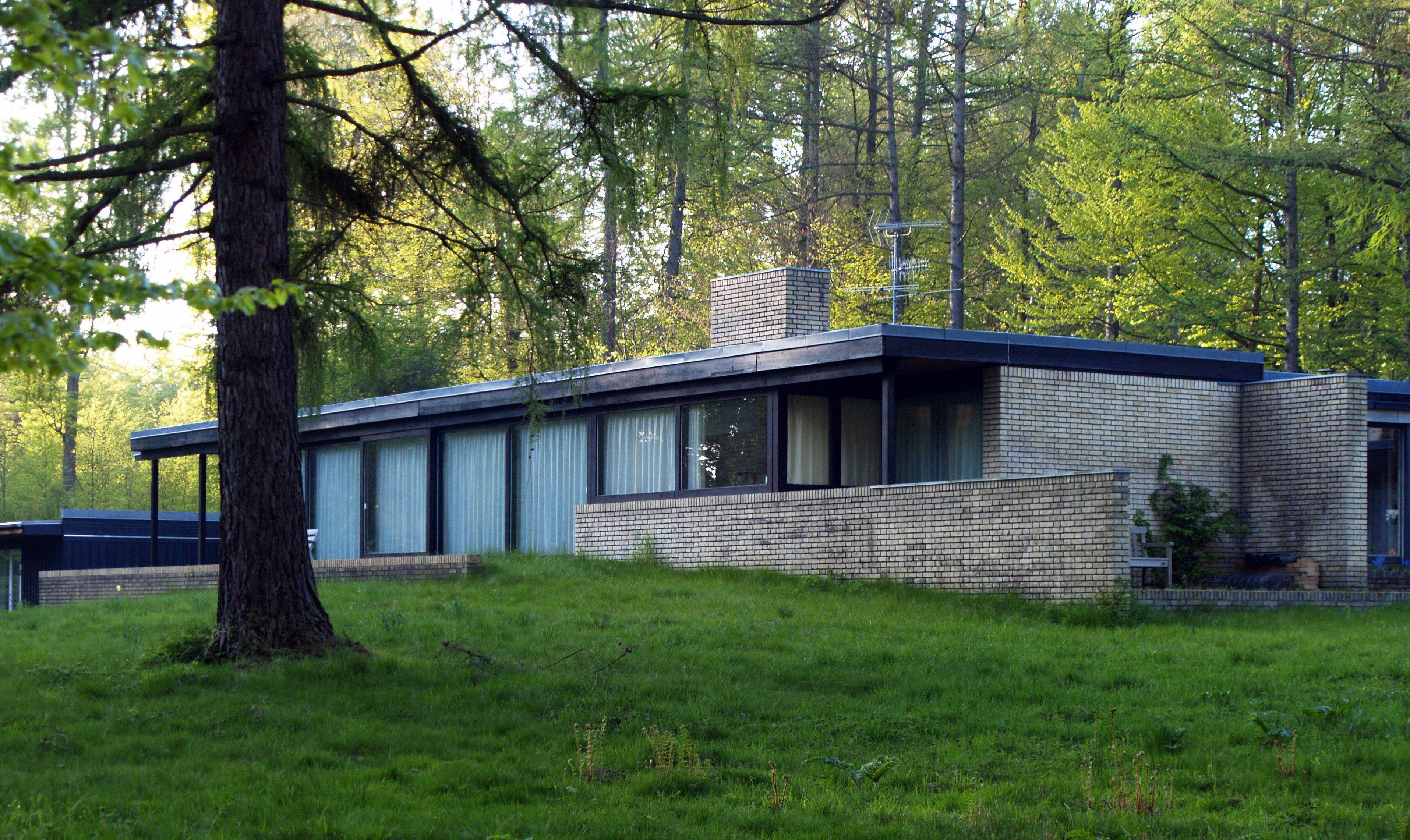 ranch-type hus, stort senter skorstein, glassvegger, steinvegger