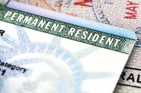 A Green Card lying on an open passport