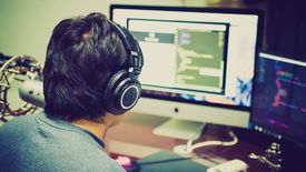 Man using multiple screens to work on coding and programming.