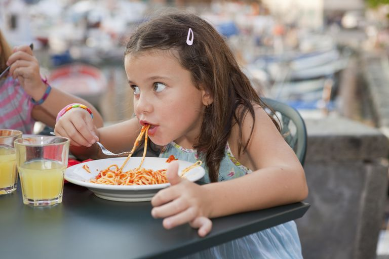 Little girl eating spaghetti in Italy