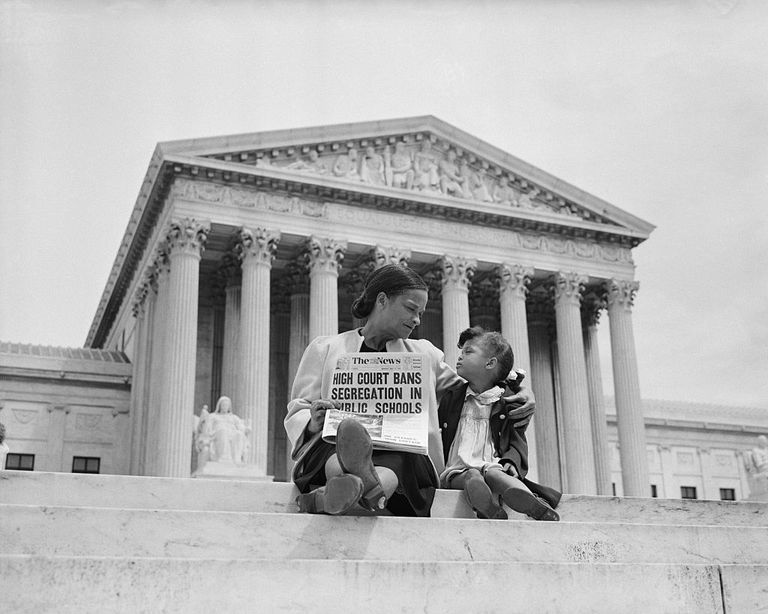 "Nettie Hunt and her daughter, Nickie, sit on the steps of the U.S. Supreme Court. Nettie holding a newspaper reading ""High courts bans segregation in public schools"""
