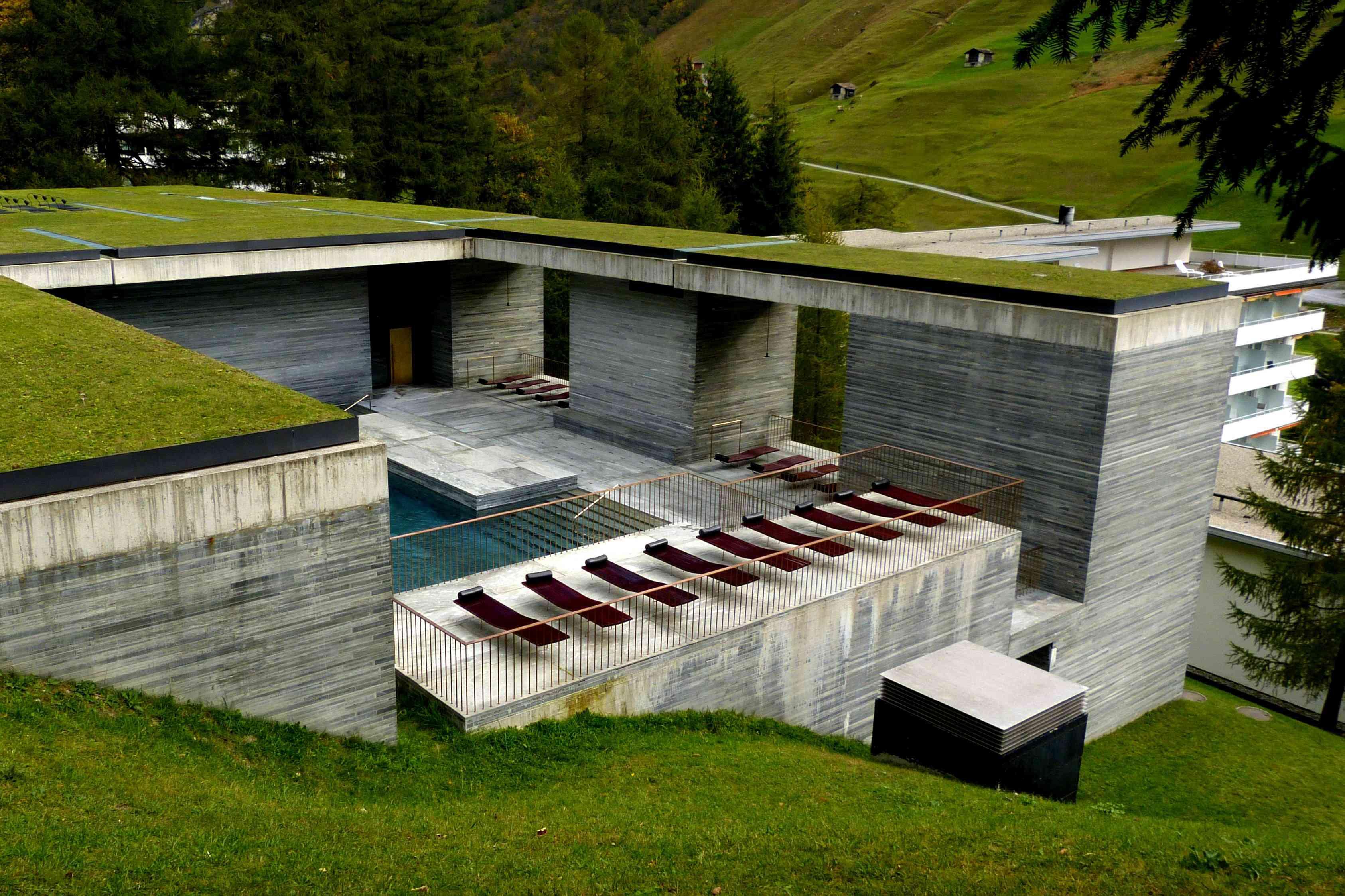 En los baños termales de Zumthor en Vals, un techo de césped verde y baños termales abiertos están sostenidos por capas de piedra que parecen paredes de madera.
