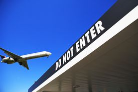 """Airliner flying over 'Do Not Enter"""" sign at airport"""