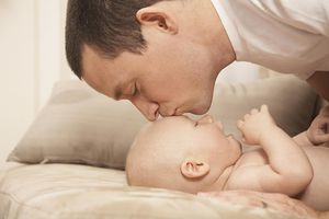 Father kissing baby's forehead.