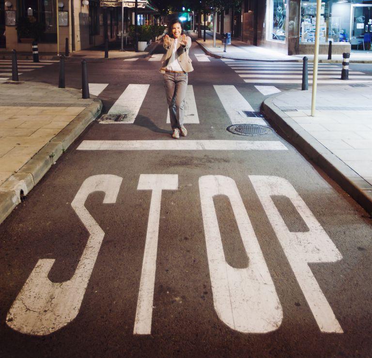 Mujer señalando letrero de Stop en una calle.