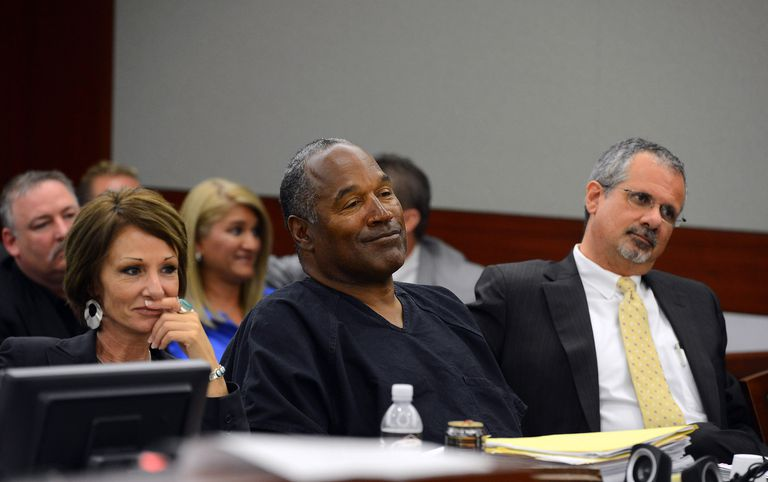 O.J. Simpson sitting in court smiling with his two representatives.