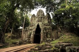 The East Gate at Angkor Thom surrounded by jungle.