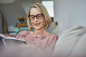 Smiling woman at home on the sofa reading a book