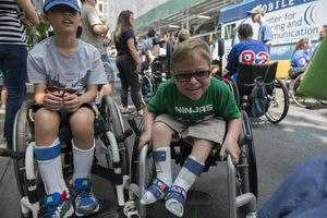A boy with spinal bifida shares a laugh with friends