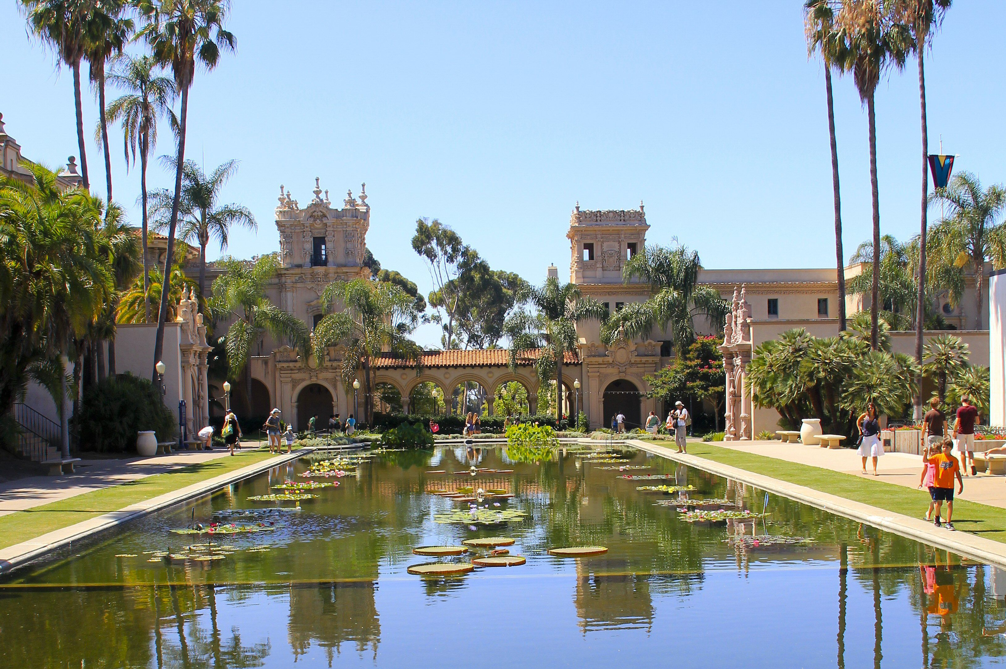 two towers connected by arched walkway with a landscaped pond in the foreground
