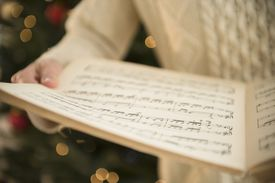 A person standing in front of a Christmas tree holds sheet music