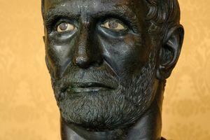 Close up of bust of Lucius Junius Brutus against orange background.