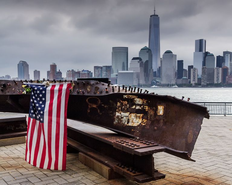 The New York City skyline without the Twin Towers, an American flag and twisted metal in the foreground.