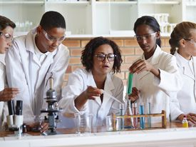 Teacher helping students with test tubes & pipette