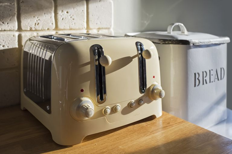 A toaster and bread box on a sunny kitchen counter