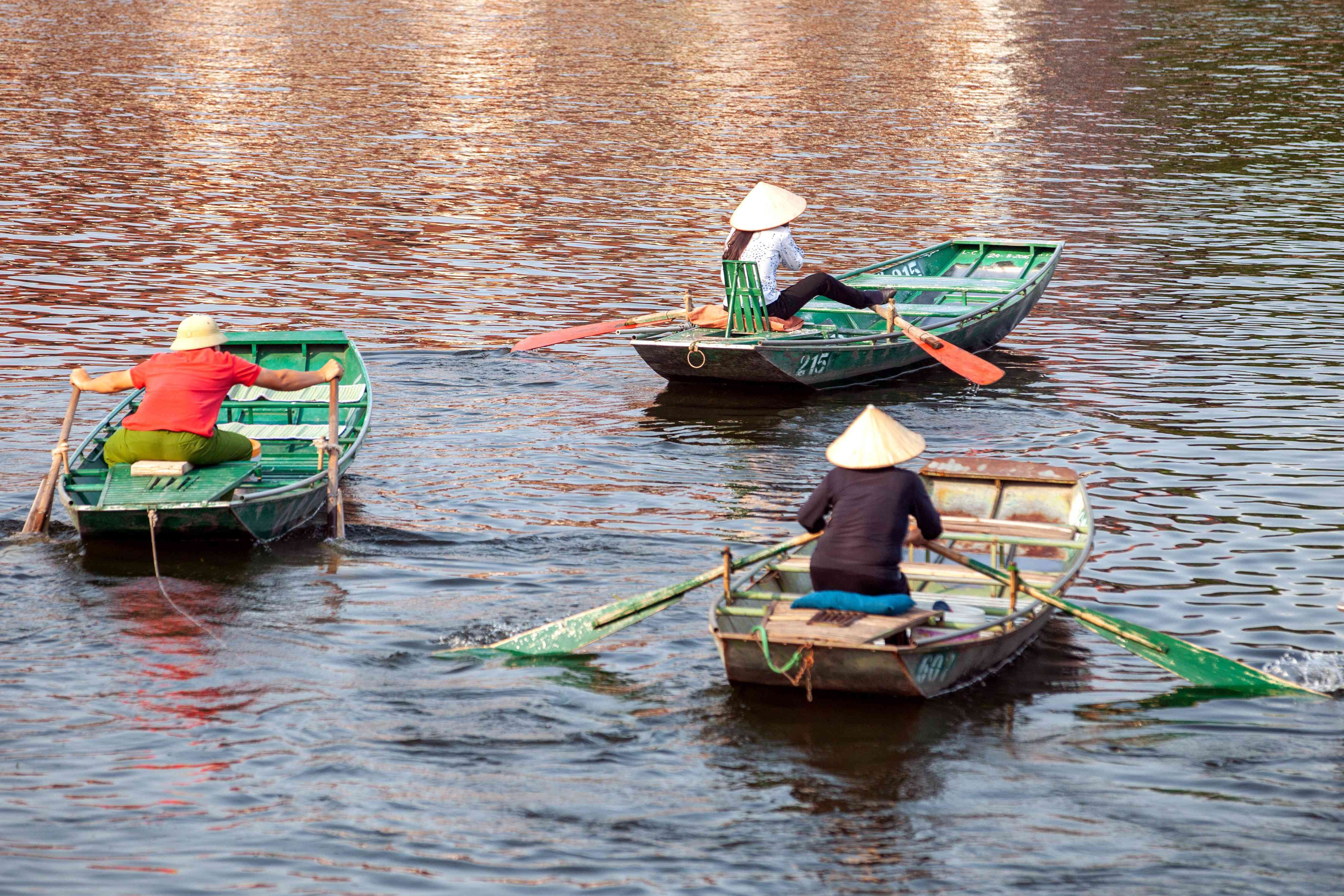 Paddlers on simple rowboats in Vietnam traverse the Red River Delta