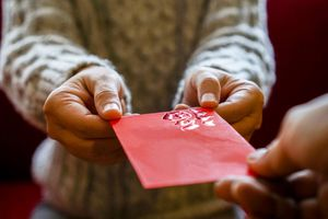 Close up of one person giving a red envelope to another.