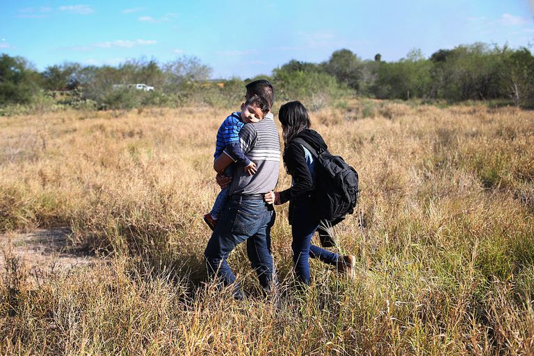 A father carries his sleeping son, 3, after their family illegally crossed the U.S.-Mexico border on December 7, 2015 near Rio Grande City, Texas.