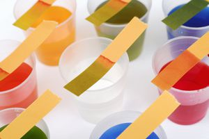 Litmus test strips on top of plastic cups with various multicolored liquids