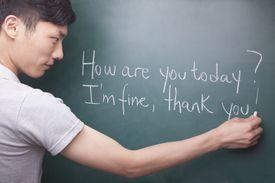 Young man writing English sentences on the blackboard
