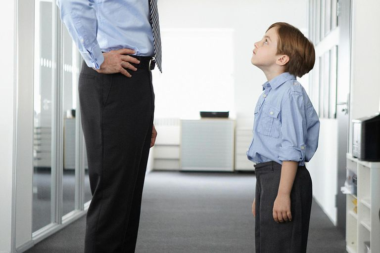 Father and son standing face to face in office