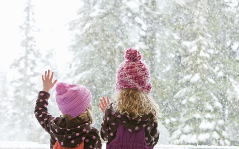 Young sisters look at snowfall outside