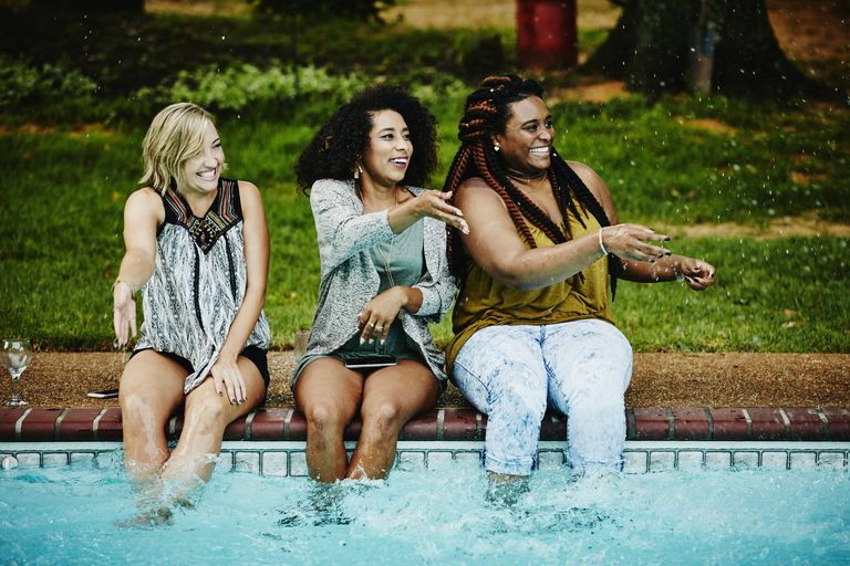 Women sitting on edge of pool splashing friends