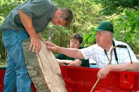 Dr. Alex Shigo pointing out markings on an Oak section on a red pickup truck
