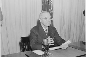 President Truman delivering a radio address speaking into a microphone on a desk.