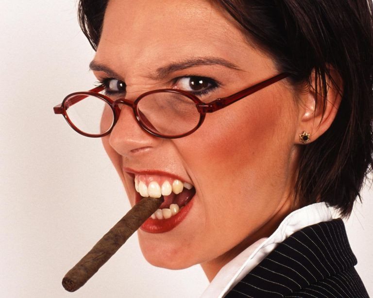 Businesswoman smoking cigar, portrait