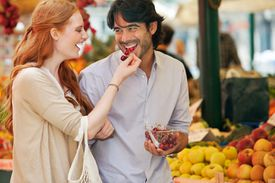 man eating cherry fed to him by a woman