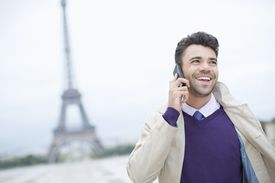 Businessman talking on cell phone by Eiffel Tower