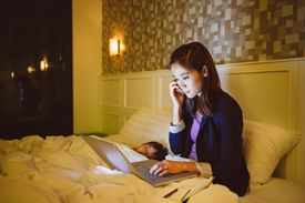 A business woman working from bed while her child sleeps next to her symbolizes a common form of role conflict that many working mothers experience.