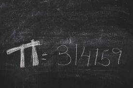 Hand-written Pi numbers on a black chalkboard