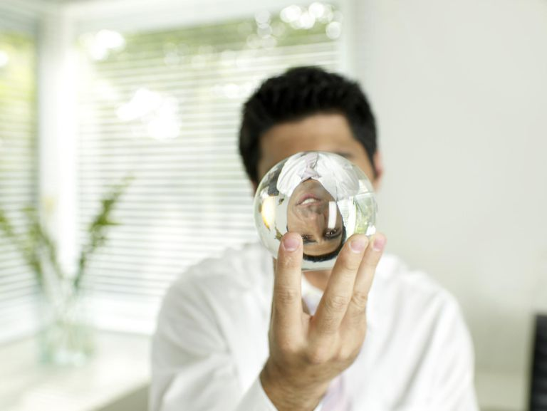 Businessman holding crystal ball, face reflecting on ball
