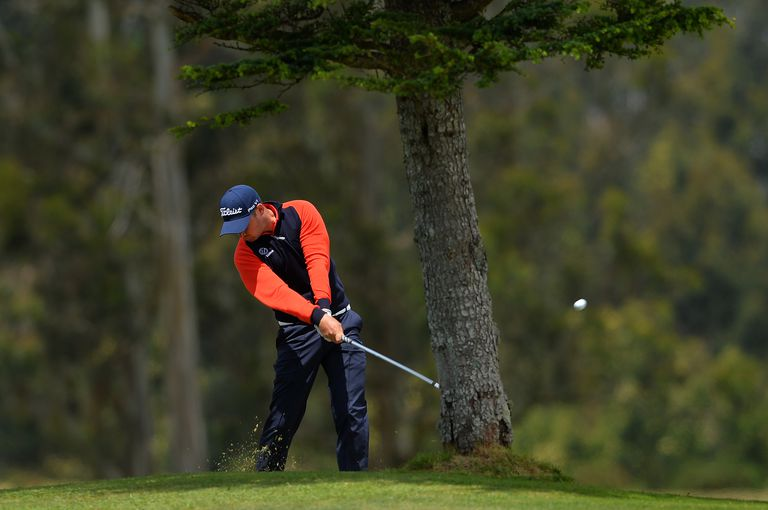 Golfer Daniel Brooks plays from behind a tree during the Madeira Islands Open tournament