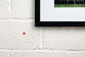 A small orange sticker beside a work of art indicates that is has been purchased