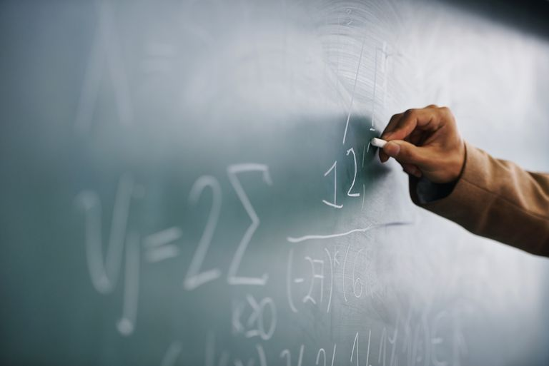 Hand writing formulas on a chalkboard