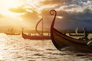 Viking ships on the water under the sunlight and dark storm