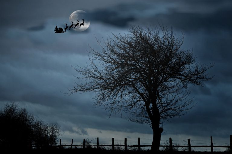 Silhouette of Santa Claus riding his sleigh against a night sky.