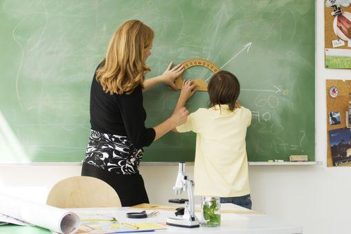 Teacher helping boy draw angle on blackboard using protractor, rear view