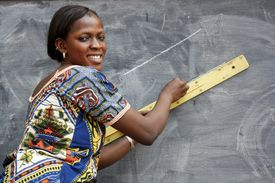 a woman drawing a line with a ruler on a chalk board