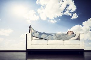 man laying on couch with clouds in the sky