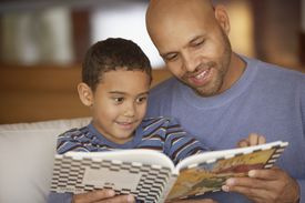 Father and son reading book while sitting on couch