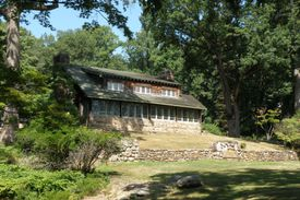 wooded lot, house with large front windowed porch, side gable, stone chimney, wide shed dormer