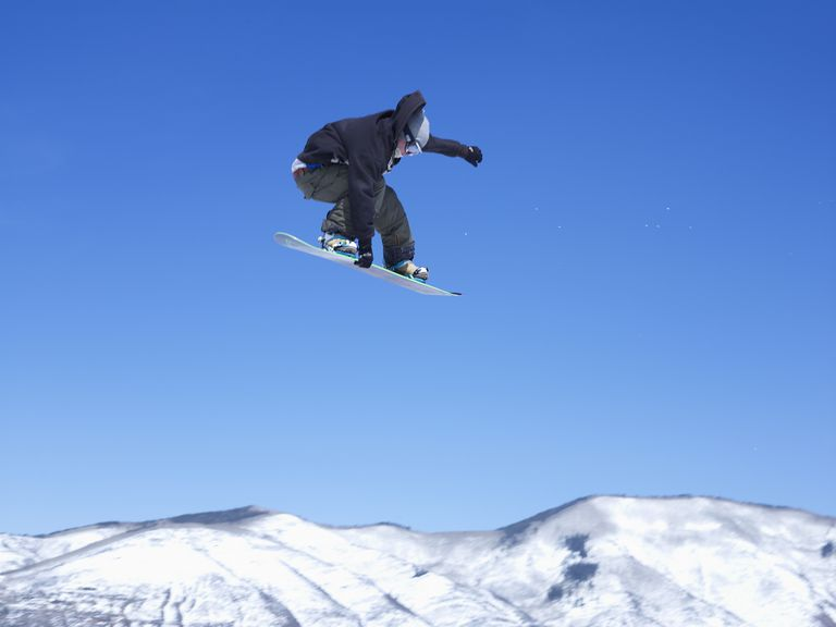 Man snowboarding, jumping in mid-air, low angle view